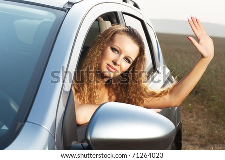 Young woman looking out of car and waving hand. - stock photo