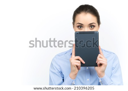 young woman looking out of digital tablet. beautiful girl holding tablet over her face on white background