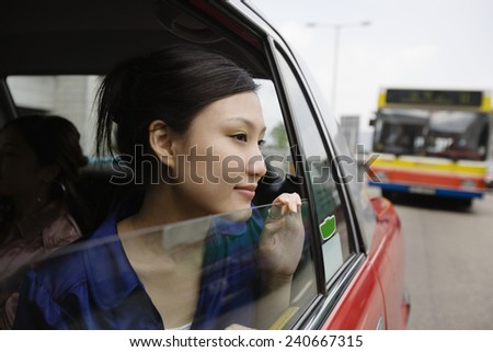 Young Woman Looking out Through the Window of a Taxi