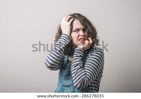 Young woman looking scared - stock photo