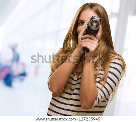Young Woman Looking Through A Camera against an abstract background - stock photo