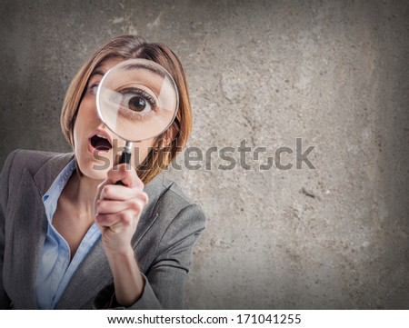 young woman looking through a magnifying glass against a grunge wall