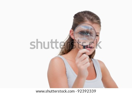 Young woman looking through a magnifying glass against a white background