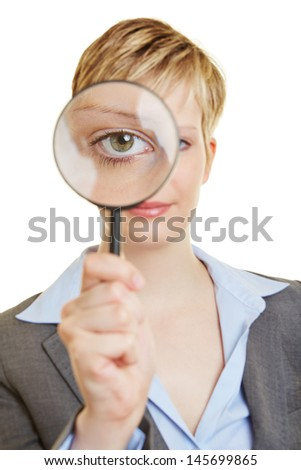 Young woman looking through a magnifying glass with her eye