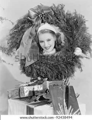 Young woman looking through a wreath with presents in front of her - stock photo