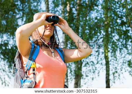 Young woman looking through binoculars on a summer nature - stock photo