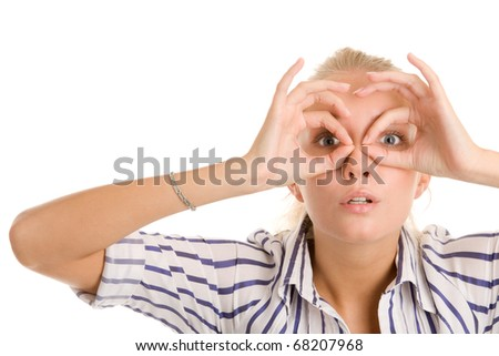 Young woman looking through circled fingers - stock photo