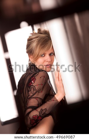 Young woman looking through frame - stock photo