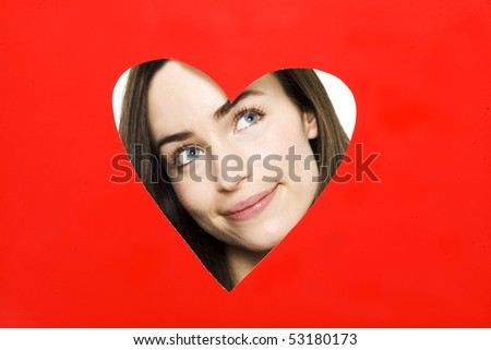 young woman looking through heart shape - stock photo