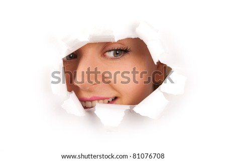 Young woman looking through hole in a paper - stock photo