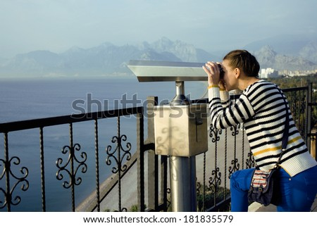 young woman looking through telescope at sea viewpoint in Ataturk park - stock photo