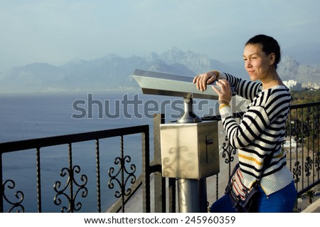 young woman looking through telescope at sea viewpoint in Ataturk park smiling - stock photo