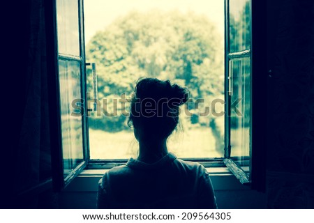 Young woman looking through the window on the garden or forest in the countryside. Vintage filter. Blue tone. - stock photo