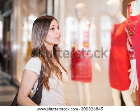 Young woman looking to a shop window - stock photo