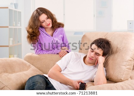 Young woman looking to her boyfriend asleep on sofa at home