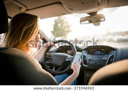 Young woman looking to her smartphone while driving car - rear view, sun shines through front window - stock photo