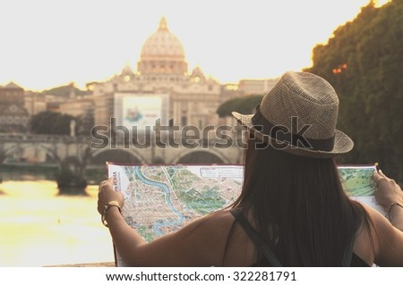 Young woman looking to the Rome map across the San Pietro Basilica. - stock photo
