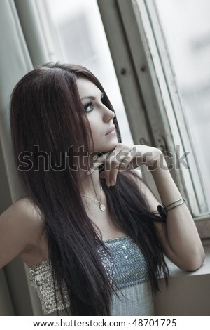 Young woman looking to the window portrait. - stock photo