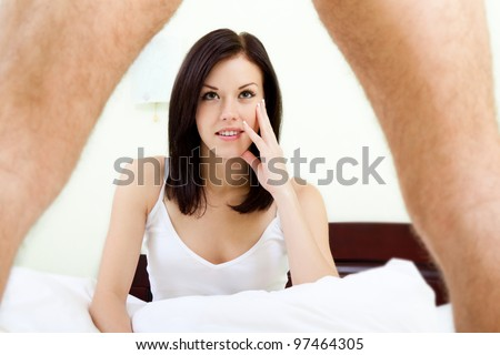 young woman looking under man leg, sho?k, sitting on bed in her bedroom, concept
