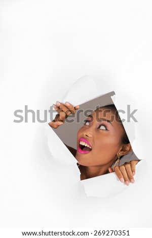 Young woman looking up through the hole in white paper - stock photo