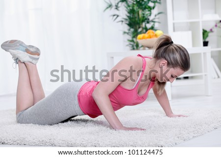Young woman looking up while doing push-ups in living room - stock photo