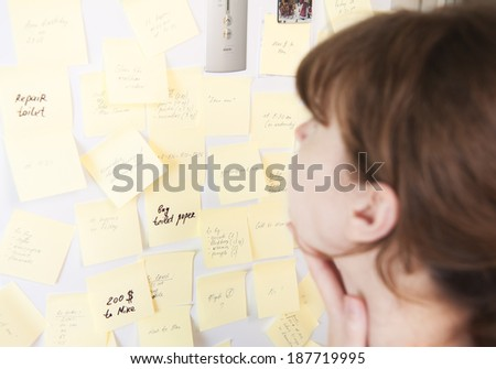 Young woman looks at stickers on refrigerator. Planning and time management crisis. Confusion.