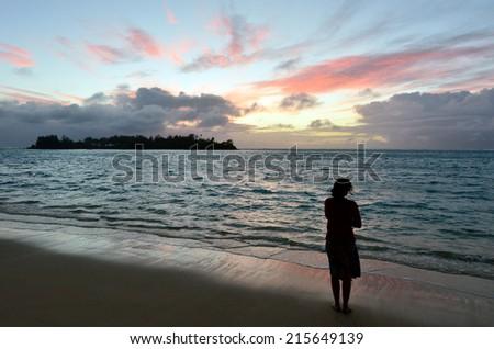 Young woman looks at the sunrise of tropical Island on Muri lagoon in Rarotonga, Cook Islands. - stock photo