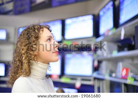 Young woman  looks at TVs in shop - stock photo