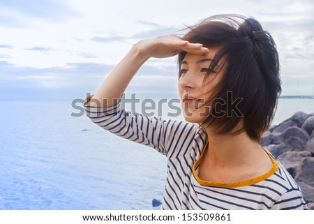 Young woman looks into the distance at sea