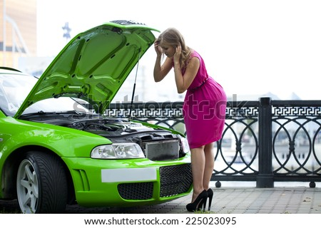 Young woman looks into the open hood on the summer street - stock photo