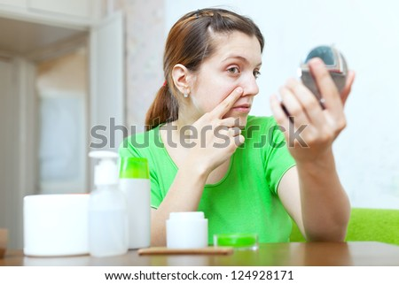 Young woman looks on her face in mirror at home - stock photo