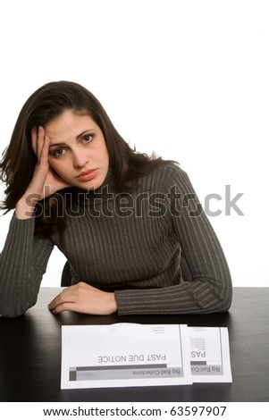 Young woman looks sad with past due notices in front of her - stock photo