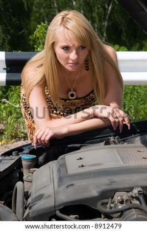 Young woman looks under a cowl of the car.