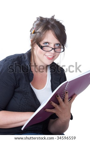 Young  woman looks up from reading her planner; isolated on a white background. - stock photo