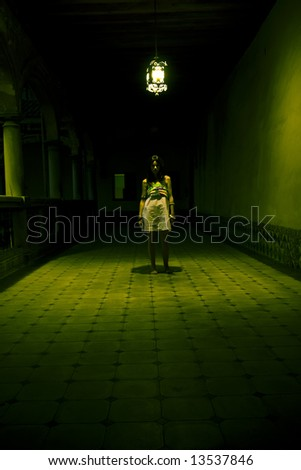 Young woman lost in spooky dirty corridor. - stock photo