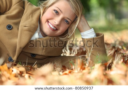 Young woman lying amidst autumnal foliage in the woods