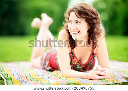 Young woman lying down in park enjoying the summer - stock photo