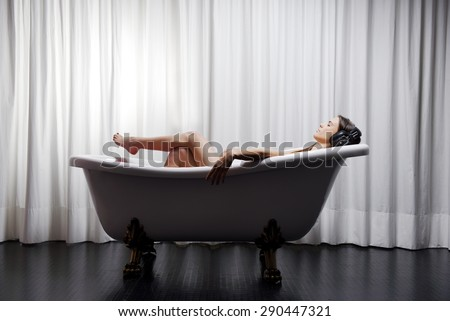 Young woman lying in a bathtub listening to music with big headphones on her head. Concept of relaxation and freedom. - stock photo