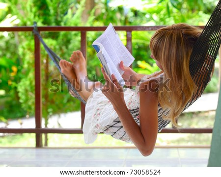 Young woman lying in a hammock and reading a book - stock photo