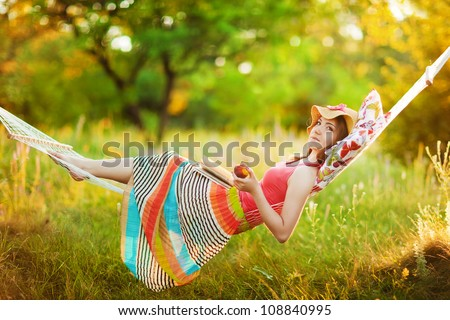 Young woman lying in a hammock in garden and reading a book - stock photo