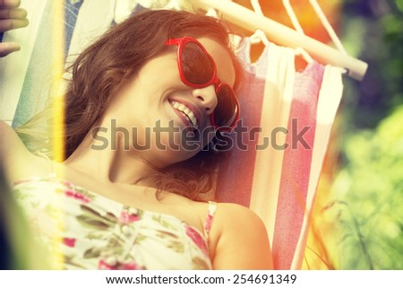 Young woman lying in a hammock in garden on summer. - stock photo