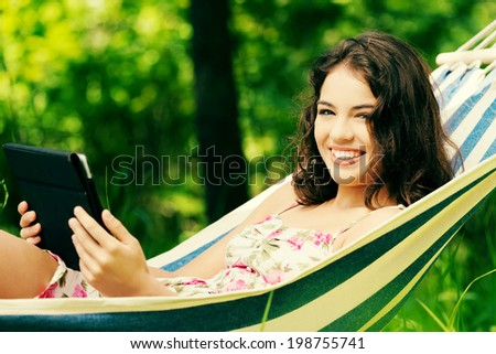 Young woman lying in a hammock in garden with E-Book on tablet computer. - stock photo