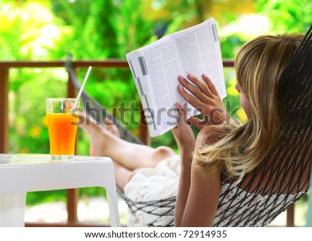 Young woman lying in a hammock in green garden and reading a book - stock photo