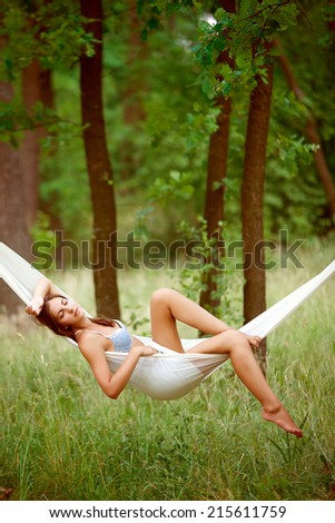 Young woman lying in a hammock on resort