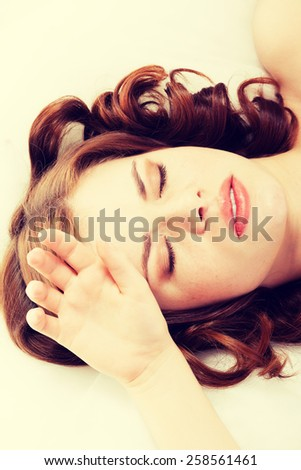 Young woman lying in bed having headache. - stock photo