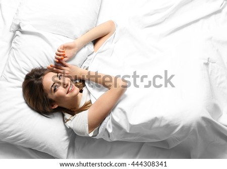 Young woman lying in bed, top view - stock photo