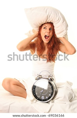 young woman lying in bed with alarm clock - stock photo