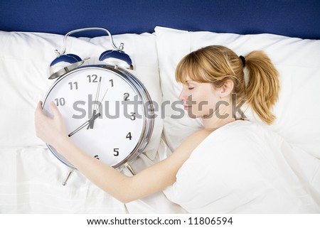 Young woman lying in bed with eyes closed, holding a huge alarm clock - stock photo