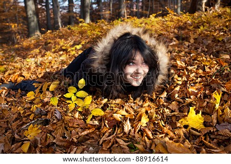 Young woman lying in fallen autumn leaves
