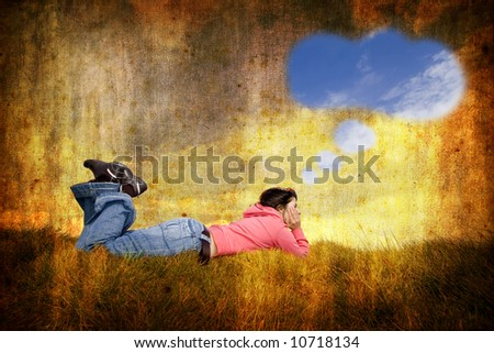 young woman lying in grass with speech balloon - stock photo